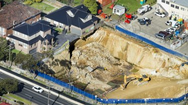 Two townhouses sit on the edge of a crumbling construction pit on the corner of Huntingdale and Highbury Roads, Mount Waverley. All practitioners involved are under investigation.
