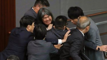 """Lawmaker Leung Kwok-hung, known as """"Long Hair,"""" top centre, tries to break through the security guards during the election of president of the Legislative Council in Hong Kong."""