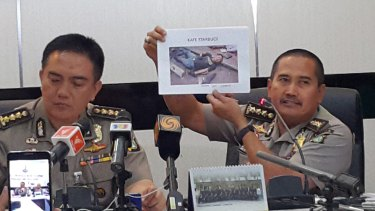 Jakarta policeman Muhammad Iqbal (left) and Musyafak show a photo the body of gunman Sunakim who was killed in the blast.