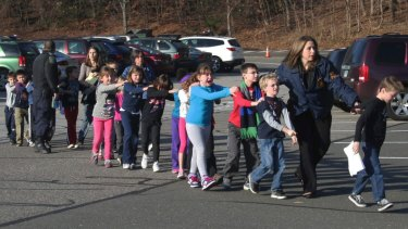 Police lead children from the Sandy Hook Elementary School in Newtown, Connecticut, where 26 people were killed in December 2012. The United States has about one school shooting a month.