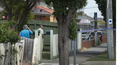 Concerned neighbours survey the scene of a homicide investigation in Thomastown.