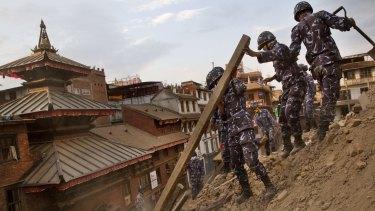 Nepalese policemen clear the debris at Basantapur Durbar Square, damaged in Saturday's earthquake, in Kathmandu.