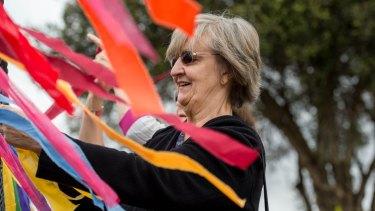 Carmel Rafferty tying ribbons on the fence outside the Holy Family parish, Doveton on Good Friday.