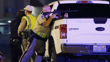 A police officer takes cover behind a truck at the scene of a shooting  on the Las Vegas Strip.
