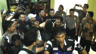 Handcuffed, David Taylor arrives at Denpasar police station on Friday.