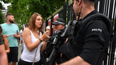 A woman offers her ice cream to a police officer as armed police patrol around Old Trafford Cricket Ground ahead of a Courteeners concert ahead of the One Love benefit set to take place on Sunday night.