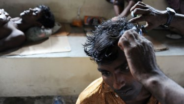 A rescued migrant receives a haircut at a temporary shelter in Aceh.