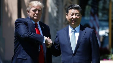 US President Donald Trump and Chinese President Xi Jinping pause for photographs on Friday.