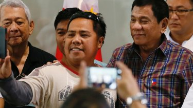 Philippine President Rodrigo Duterte, right, poses for a selfie with a returning Filipino worker.
