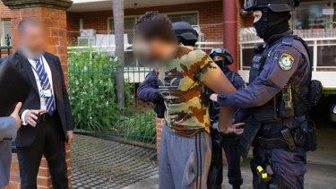 Mohamed Almaouie is taken into police custody in Bankstown.