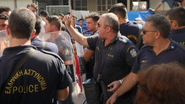 Greek riot police try to keep some order inside the stadium in Kos on Thursday.