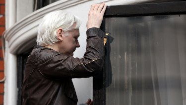 Julian Assange makes his way back indoors after speaking to the media.
