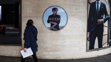Commuters walk past the Dior Sauvage advertisement featuring Johnny Depp outside David Jones' Sydney CBD store.