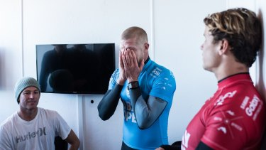 Mick Fanning holds his head in his hands in disbelief after being attacked by a shark during the final of the JBay Open while fellow finalist Julian Wilson (red) looks on.