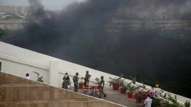 Black smoke rises in the background as Indian security officers take shelter on the roof of a government building after Dera Sacha Sauda sect members went on a rampage in Panchkula, India.