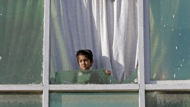 An Afghan child boy looks out from the broken window of a house near the site of a bomb attack.