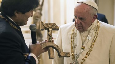 Pope Francis is presented a gift of a crucifix carved into a wooden hammer and sickle, the Communist symbol uniting labour and peasants, by Bolivian President Evo Morales in La Paz, Bolivia.