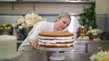 Claire Ptak, owner of Violet Bakery puts the finishing touches to one tier of the cake.