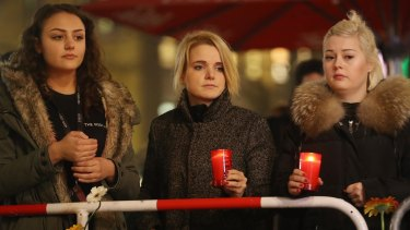 Young women hold candles at a makeshift memorial at the scene of the Berlin Christmas market attack.