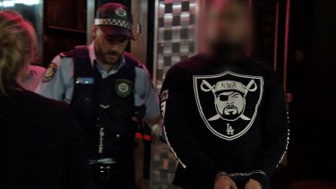 A man is taken away by police outside Bada Bing during raids in December.