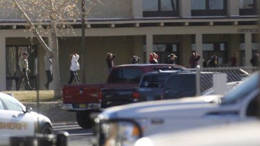 Students are led out of Aztec High School after a shooting in Aztec, New Mexico.