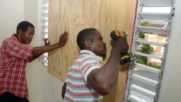 A worker nails a board to use on a storefront window as protection against hurricane Matthew in Kingston.