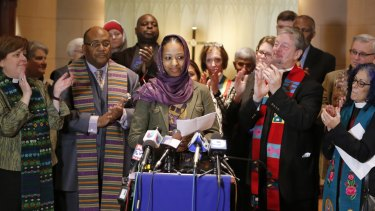 """Larycia Hawkins, centre, a professor at  Wheaton College, is greeted with applause from supporters at a news conference on December 16 after being placed on leave. Dr Hawkins, a Christian teaching political science at the private evangelical school west of Chicago,  began wearing a hijab to counter what she called the """"vitriolic"""" rhetoric against Muslims in recent weeks."""