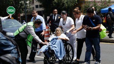 A woman in a wheelchair is evacuated from a clinic in Mexico City.
