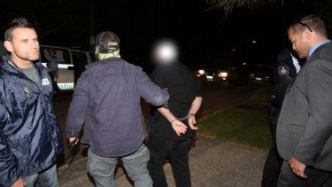 Terrorism arrests: A man is taken away in handcuffs in Marsfield.