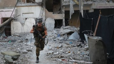 A US-backed Syrian Democratic Forces fighter runs in front of a damaged building as he crosses a street on the front line, in Raqqa, Syria in July.
