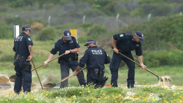 Police dig in the sand where the baby was found.