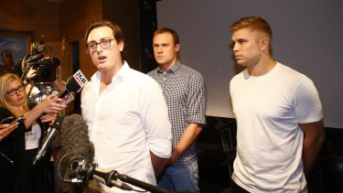 Nick Kelly, one of the nine Australians who stripped at the Formula One in Malaysia last weekend, delivers a statement at Sydney International Airport on their return. Behind him are Thomas Laslett and Edward Leaney, right.