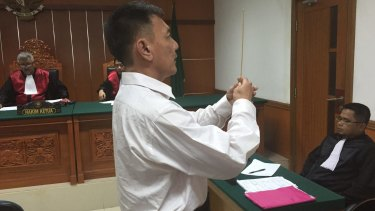 Lim Jit Wee takes an oath before testifying in West Jakarta District Court that he didn't know Christian at the time of his arrest.
