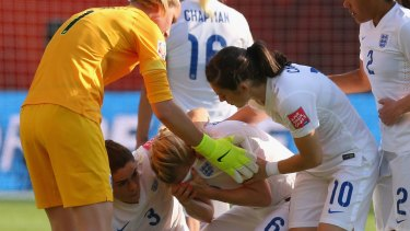 Teammates rush to comfort Laura Bassett after her own goal eliminated England.