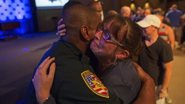 East Baton Rouge Sheriff officer Eddie Guidry is comforted by Terri Carney. Both are members of the Rock Church, which has held a prayer vigil for the officers killed and wounded in Baton Rouge on Sunday.