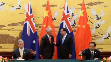 Prime Minister Malcolm Turnbull listens to Chinese Premier Li Keqiang  during a ceremony at the Great Hall of the People in Beijing.