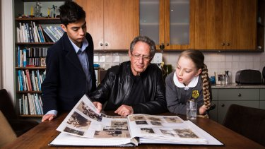 Holocaust survivor Peter Halas shows (L-R) Alex Tofler and Lily Shrire a photo album of his family that were affected by the holocaust.