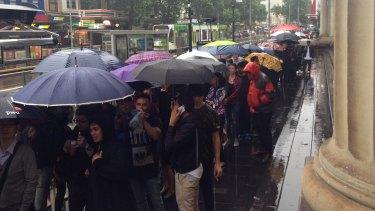 Shoppers queue in the rain along Elizabeth Street.