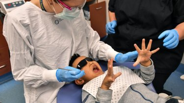 Oral health therapist Kimberley Karp helps a young patient deal with some nerves at the Royal Dental Hospital.