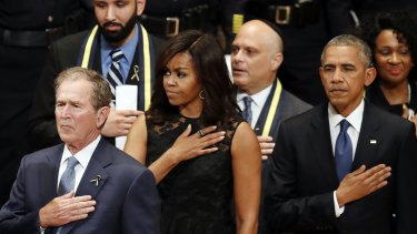 From left, former US president George W. Bush, first lady Michelle Obama and President Barack Obama stand during the interfaith memorial service.