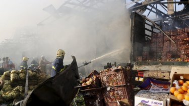 Firefighters spray water at the site of a truck bomb attack at a crowded market in Baghdad two days ago.