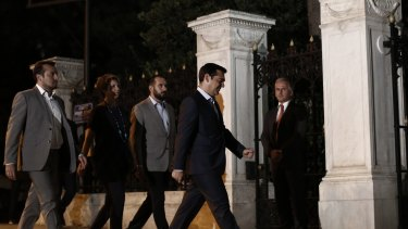 Alexis Tsipras, Greece's prime minister, second right, arrives at the presidential palace before meeting with Greek President Prokopis Pavlopoulos on Thursday
