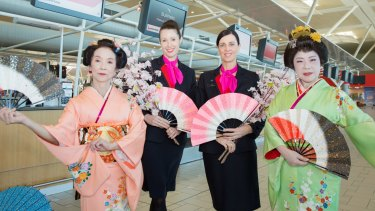 Qantas staff celebrating flights into Asia at Brisbane Airport.