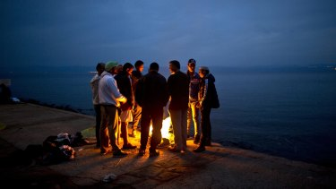 Afghan refugees gather around a fire after arriving on the Greek island of Lesbos from the Turkish coast.