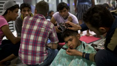 A boy gets his hair cut at a refugee and migrant camp inside Keleti train station in Budapest, Serbia.