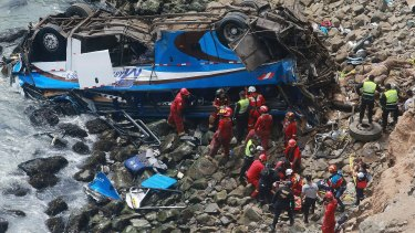 Firemen recover bodies from a bus that fell off a cliff in Peru after it was hit by a tractor-trailer rig.