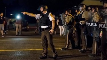 August 2015: Police on the streets of Ferguson, Missouri, during demonstrations the night after an 18-year-old black man, Tyrone Harris, was shot and wounded by police during protests marking the first anniversary of the fatal police shooting of Michael Brown.