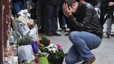 Grief stricken: A man lays flowers at the scene of one of the attacks, in front of the Carillon cafe, in Paris.