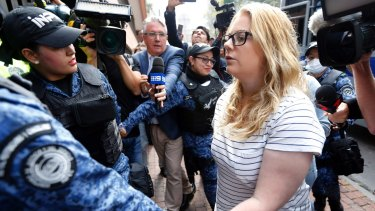 Cassandra Sainsbury is escorted by police to a court hearing in Bogota, Colombia.