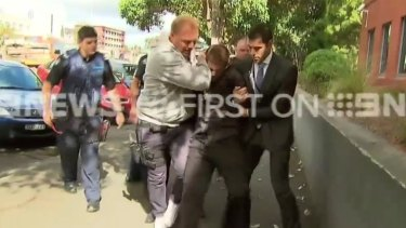 Bradley John Azzopardi puts up a fight on his way into court.